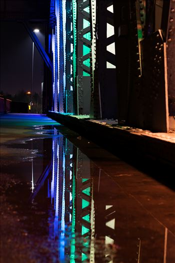 A photo of the lights on Newport Bridge and a puddle reflection.